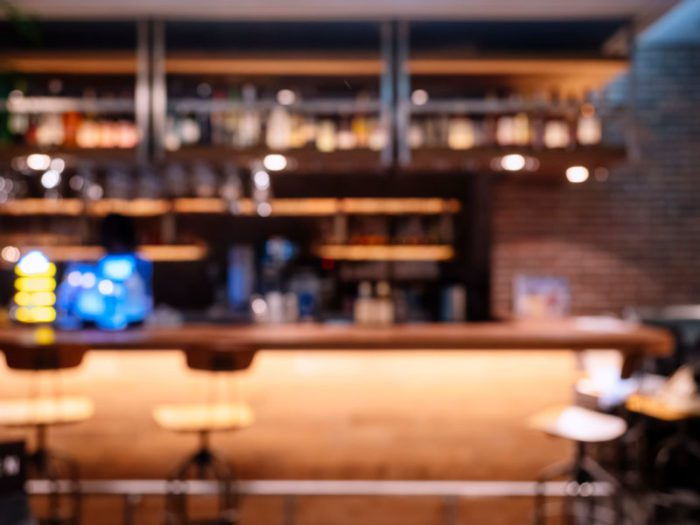 Blurred image of empty stools at a bar