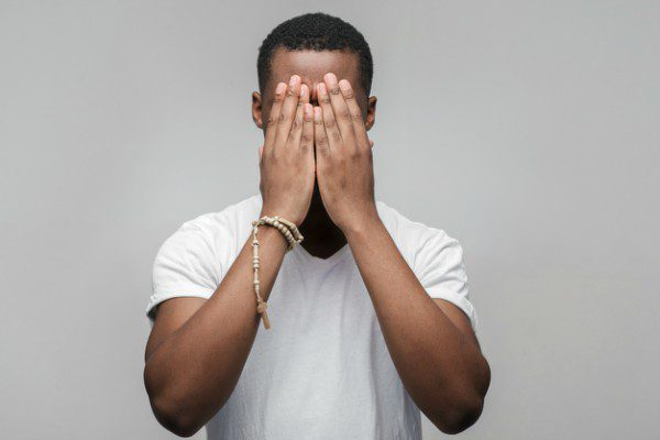Frustrated black man hiding face