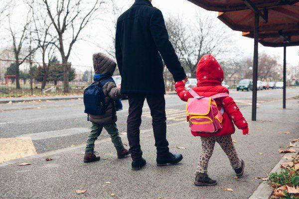 Dad walking his kids to school