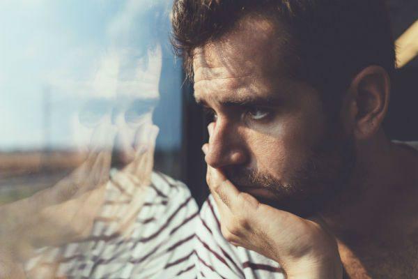 Depressed man by window