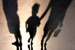 Mother holding childs hand in shadow