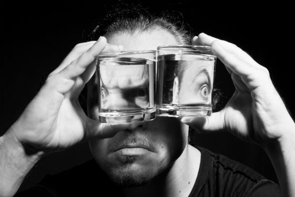 Bipolar man looking through drink glasses